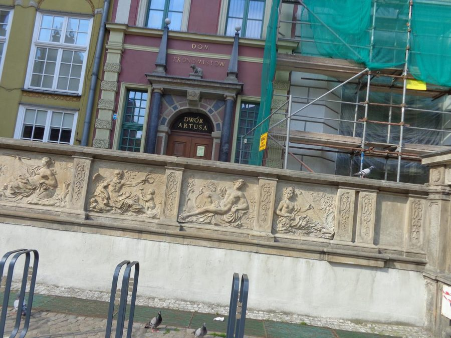 A wall with stone panels depicting classical scenes close to Neptune's Fountain. Behind is Artus Court (partly obscured by scaffolding). This Dutch Mannerist building dates from the 14th century with the current façade constructed between 1616-1618 by Abraham van den Blocke.