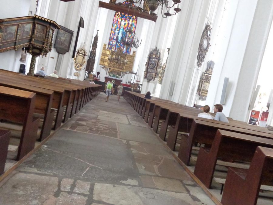 View along the aisle inside St Mary's Church with wooden pews at the sides. The main altar is at the end with a colourful stained-glass window above. A raised pulpit is also visible to the left.