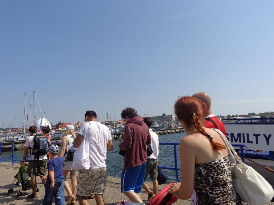Ferry passengers leaving Hel Harbour. Small boats visible and the town beyond.