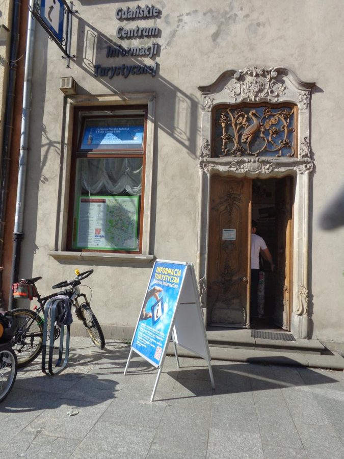 Interesting doorway to tourist office on Long Market (Długi Targ). Decorative carved wooden doors and surrounding stone work (curvy and naturalistic design). A skylight above with overlaid wooden carving, including a stork in the centre.