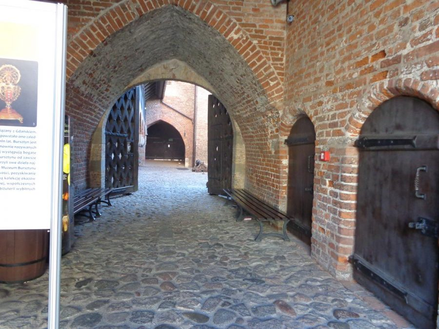 View inside Prison Tower. An arched brick passageway with heavy wooden doors down one side. Originally built for defensive purposes, Prison Tower became a prison in the 17th century, and is today a museum.