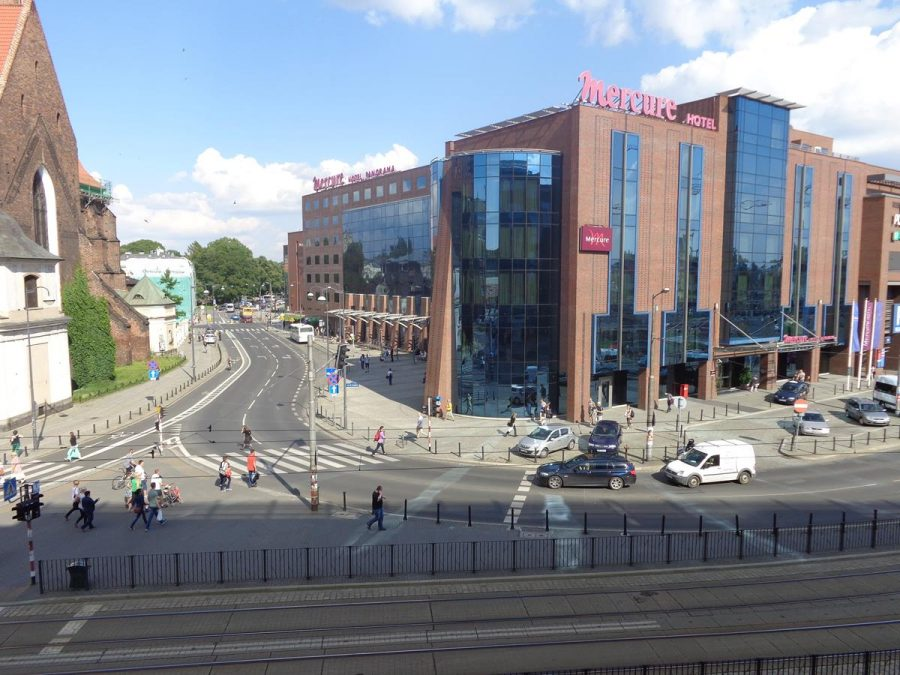 View across a road with tram tracks running in the foreground. The large modern Mercure Hotel, built of brick and glass, is opposite. To the left, a small part of St Adalbert's Church can also be seen. These are located on the east side of Wrocław's historic centre.