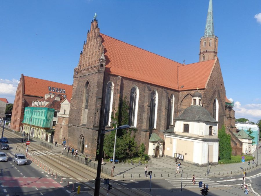 Looking towards St Adalbert's Church, which was founded in 1112, and was the first church on the left bank of the Oder river. It was destroyed in the 1241 Tartar invasion and again during the 1945 Siege of Wrocław at the end of World War II. The first stage of reconstruction took place between 1953 and 1955. It is built of brick in Gothic style. It has a red brick roof and at the rear a slender octagonal tower topped with a spire.