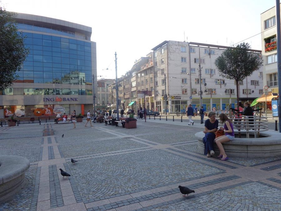 Square on the north side of St Mary Magdalene Church next to Stwosza and Szewska streets. A few people sitting on benches and pigeons wondering about.