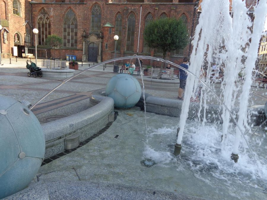 Football Fountain (Fontanna pilkarska) in a square to the north of St. Mary Magdalene Church. The fountain is a concave square shape enclosing a shallow pool. Jets of water rise from the centre and on the corners are four football-like spheres also having single jets of water spraying into the centre. The fountain is of Polish granite from Strzegom, including four decorative crystal balls of 90 cm in diameter.