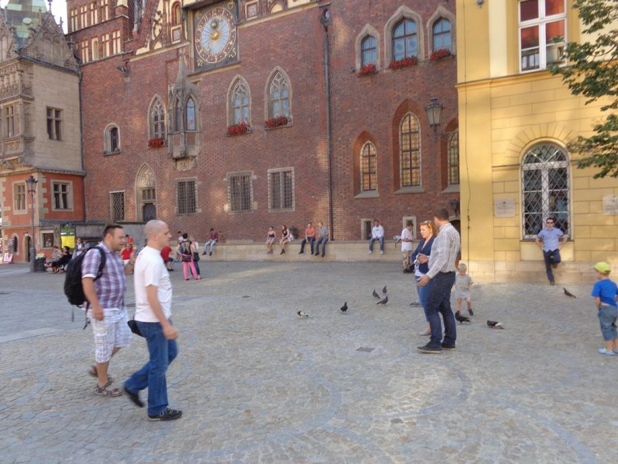 Now in the main historic Market Square (Rynek) looking towards the impressive east facade of the Old Town Hall, which features an astronomical clock. The late-Gothic Old Town Hall is located in the middle of the large rectangular square along with several other buildings.