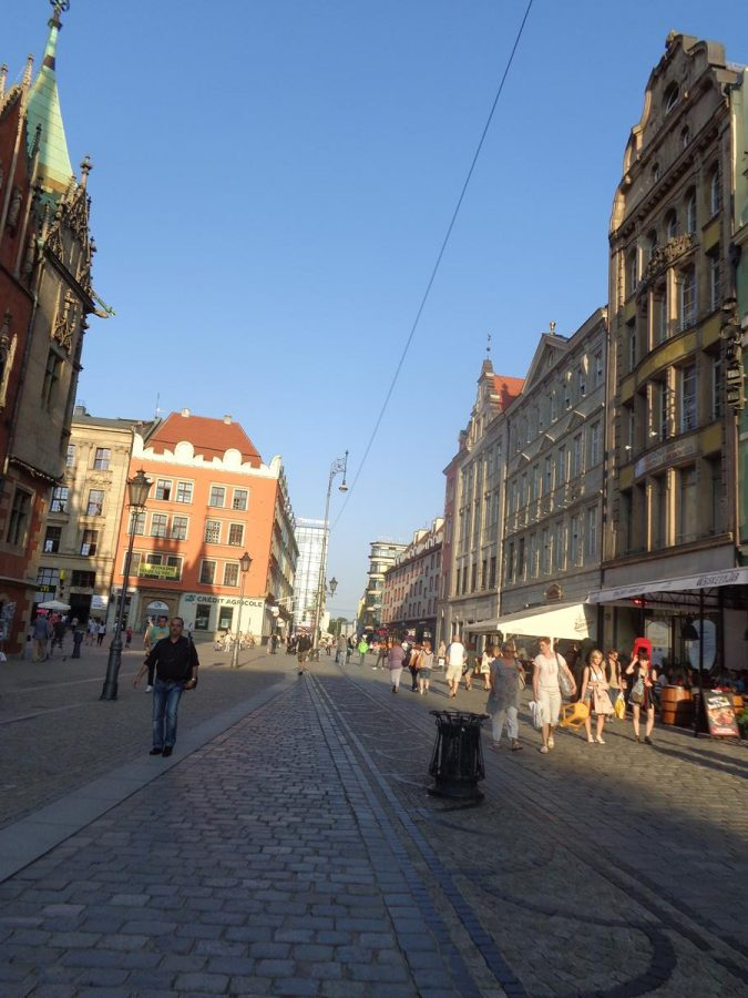View along the south side of Market Square. Historic buildings line the edges of the square, many of which were originally tenement houses. A mixture of architectural styles are in view, including Baroque. The ground floors are today mostly occupied by businesses such as shops, cafes and bars.