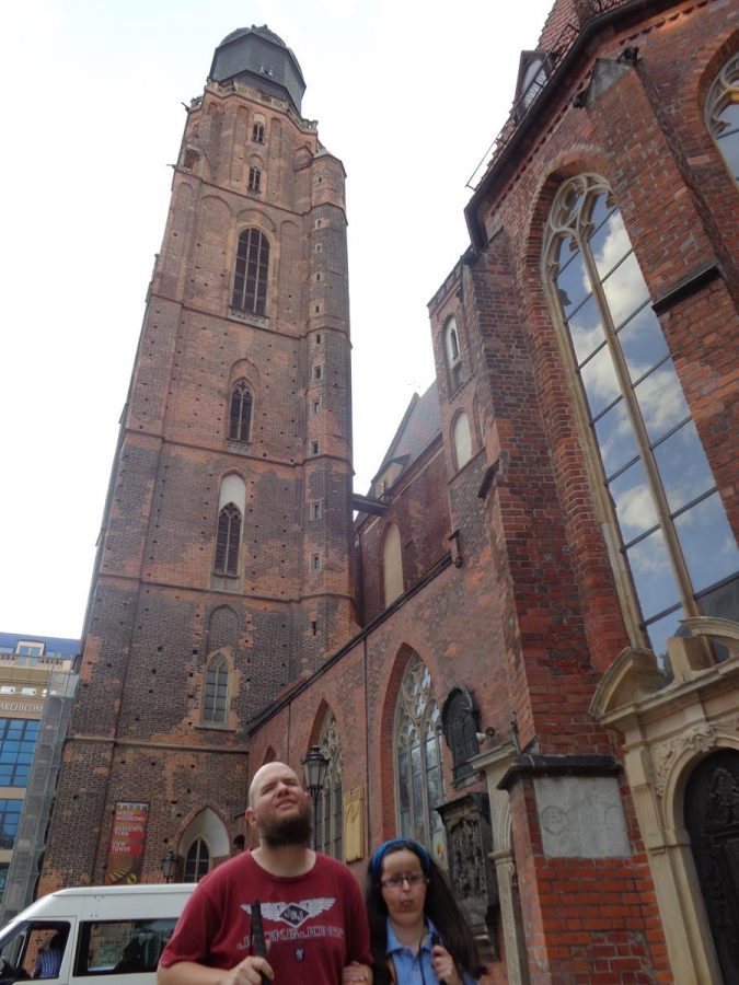 Tatiana and Tony outside St. Elizabeth's Church (Bazylika Sw. Elzbiety) with its 91.5 metre (300 foot) high tower visible above. This red brick Gothic church dates from the 14th century. From 1525 until 1946 it was a Lutheran Church, but it is today again Roman Catholic. The tower contains an observation deck.