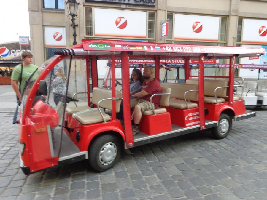 Tony and Tatiana sitting inside an open-sided electric minibus used to transport tourists around the old parts of the city on a guided tour for a fee.
