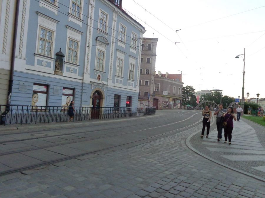 Tram tracks running in front of a blue and white Baroque building on Wyspa Piasek (Sand Island). The building was formerly a tenement house and is now a shop. The island has an area of about 5 hectares and is one of several islands in the Oder River north of the old town.
