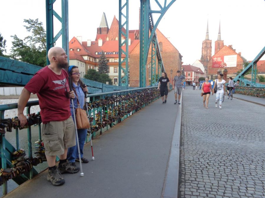 Tony and Tatiana on Tumski Bridge, a steel bridge constructed in 1889 to replace an older wooden structure. The side of the bridge has hundreds of so-called love locks (padlocks) attached to the railings. The twin towers of Wrocław Cathedral (St. John the Baptist) can be seen in the distance. These towers stand at 98 metres (322 feet).