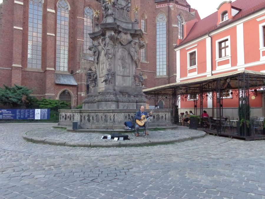 A stone monument dedicated to St. John of Nepomuk in front of the Collegiate Church of the Holy Cross and St Bartholomew on Ostrów Tumski (Cathedral Island). The monument is 9.5 metres in height and dates from 1730-1732. The upper part that depicts St. John of Nepomuk is out of view. St. John of Nepomuk is a Roman Catholic saint who lived in the 14th century. It is said he was drowned in the Vltava river at the behest of King Wenceslaus IV of Bohemia and because of the manner of his death he is a protector from floods and drowning. In front of the monument, a male busker is playing a guitar.