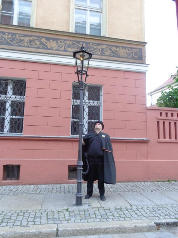 A man in a cloak and top hat lighting a gas lantern on Ostrów Tumski (Cathedral Island). There are still 102 original gas street lights on Ostrów Tumski. These are manually lit each evening.
