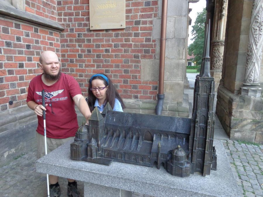 Tony and Tatiana exploring a tactile model of Wrocław Cathedral, which is officially known as the Cathedral of St. John the Baptist. A pair of stone pillars behind, outside the cathedral's main entrance. A church has stood here since the 10th century and the present brick Gothic structure was constructed in the 13th century. The cathedral was severely damaged during World War Two with initial reconstruction lasting until 1951.