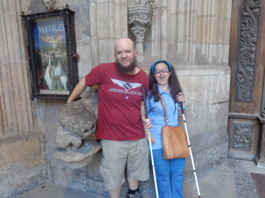 Tatiana and Tony outside the main entrance to Wrocław Cathedral. Tony is touching what appears to be a large stone head.