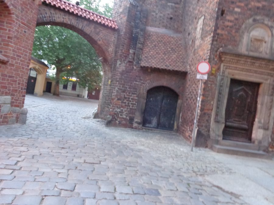 A brick archway with a narrow cobbled street passing underneath. The archway is part of St. Giles Church, the oldest surviving church in the city, and the only one to survive the Tatar invasions. It stands opposite Wroclaw Cathedral. The church was first built in the 1220s as a Romanesque church on the initiative of the dean of the cathedral chapter in Wroclaw. It was destroyed by fire in both the 17th and 18th centuries, thus perhaps leading to the construction of baroque volt in the nave. Most of the baroque additions on the church were removed after the end of World War II, leaving a modest building as seen at present.