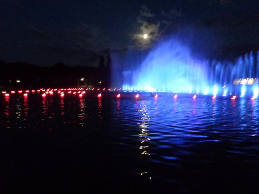 The pond now lit-up as the multimedia light and music show takes place. Some of the fountains illuminated in blue light.