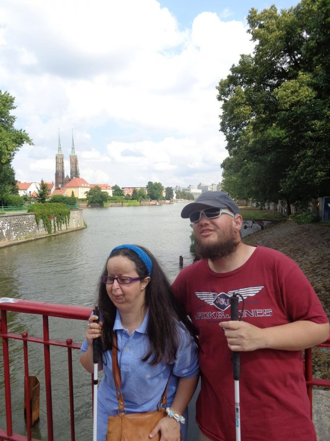 Tatiana and Tony on Piaskowy Bridge (Most Piaskowy) with another view over towards Wrocław Cathedral. A tree-lined riverside path immediately behind with Wyspa Piasek (Sand Island) opposite.