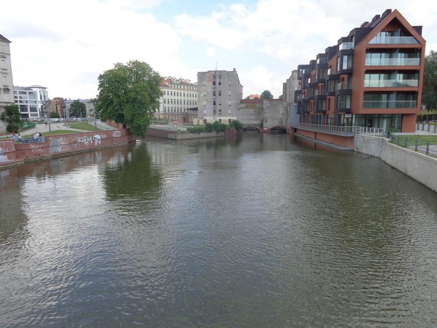 View from a footbridge connecting Wyspa Piasek (Sand Island) and Wyspa Słodowa (Malt Island). In front the channel separating the islands forks with Wyspa Młyńska (Mill Island) sitting in between. Buildings visible include modern riverside apartments and older concrete mill buildings.