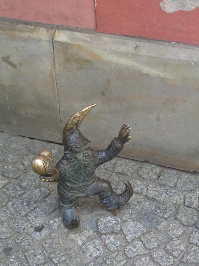 A bronze dwarf, one of over 600 to be found around Wroclaw. They are typically 20 to 30 centimetres (8 to 12 inches) in height. This one has a pointed hat and shoes and is holding a heart. This is called WrocLovek (WrocLover).