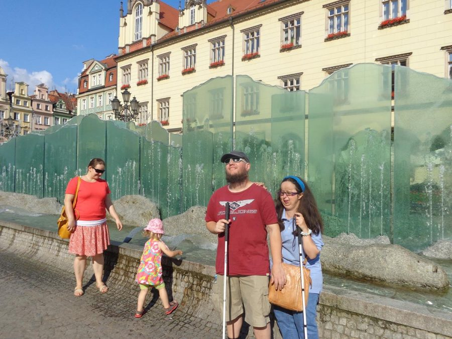"""The Zdrój Fountain (Fontanna """"Zdrój""""), located in Market Square. This long narrow fountain is made from vertical glass sheets and granite in which water runs down. It was erected in 1996, with the consent of Wroclaw Mayor, Bogdan Zdrojewski. The fountain's name """"Zdrój"""" comes from the Mayor's surname. Apparently, its design and installation was controversial! Its lack of acceptance was caused by the fountain's modern design which, arguably, doesn't fit into the monumental atmosphere of the city. Opponents call it the """"soap dish"""" or more mockingly """"urinal""""."""