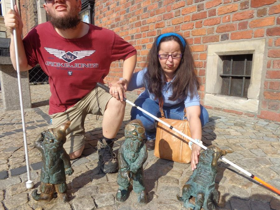This image has an empty alt attribute; its file name is DSC02151-900x675.jpgTatiana and Tony with a set of three dwarfs. The one on the right is sitting in a wheelchair, the middle one is blind and is wearing glasses and holding a cane, and the left one is hearing impaired and is holding a hand behind one ear.