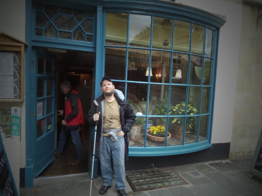 Again Tony outside Sally Lunn's. An entrance doorway and a curved bay window containing flowering plants behind.