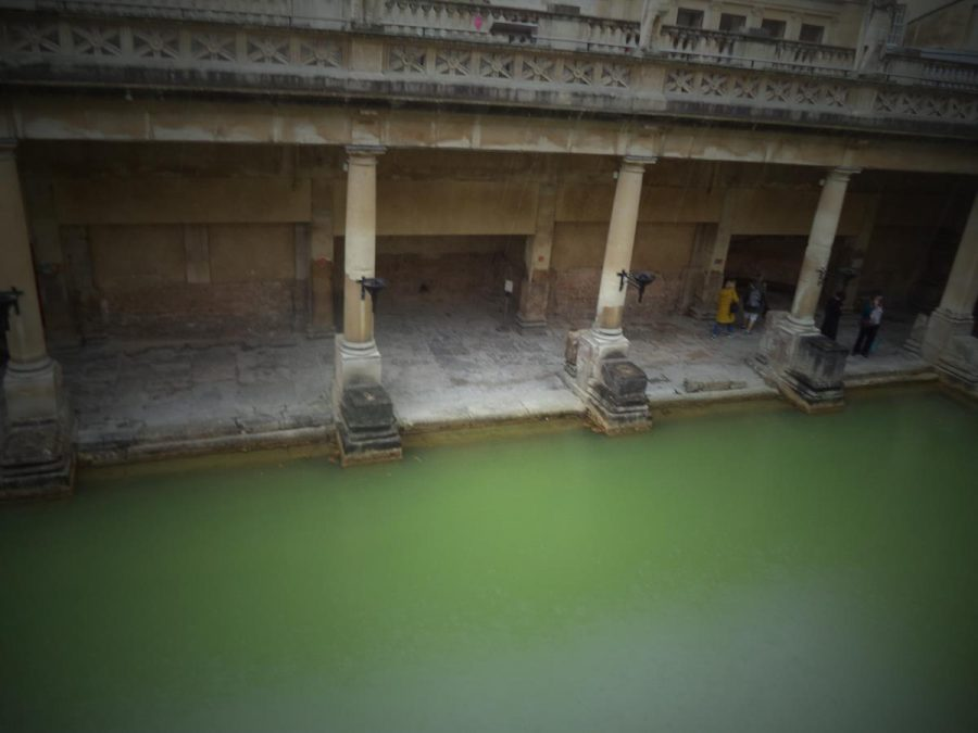 View of the Great Bath from the upper floor of the museum. The Great Bath is a rectangular pool, which is 25 metres (82 feet) long and 12 metres (39.4 feet) wide. The water is continuously warm at around 35°C and is green in colour due to the presence of algae. The pool is today open to the elements but in Roman times was covered by a roof. The sides are covered by a colonnade supported by large stone columns.