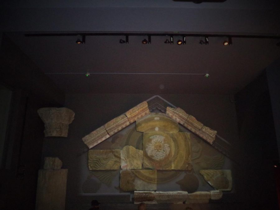 The remains of a triangular pediment from the temple with a Gorgon head at its centre. The Gorgon is a mythical figure with the face of a bearded man with serpents coming out of his hair. The pediment is 7.9 metres (26 feet) wide and 2.4 metres (8 feet) high in the centre. It would have stood atop pillars at the front of the temple building. The Bath Roman Temple stood on a podium more than two metres above the surrounding courtyard, approached by a flight of steps.