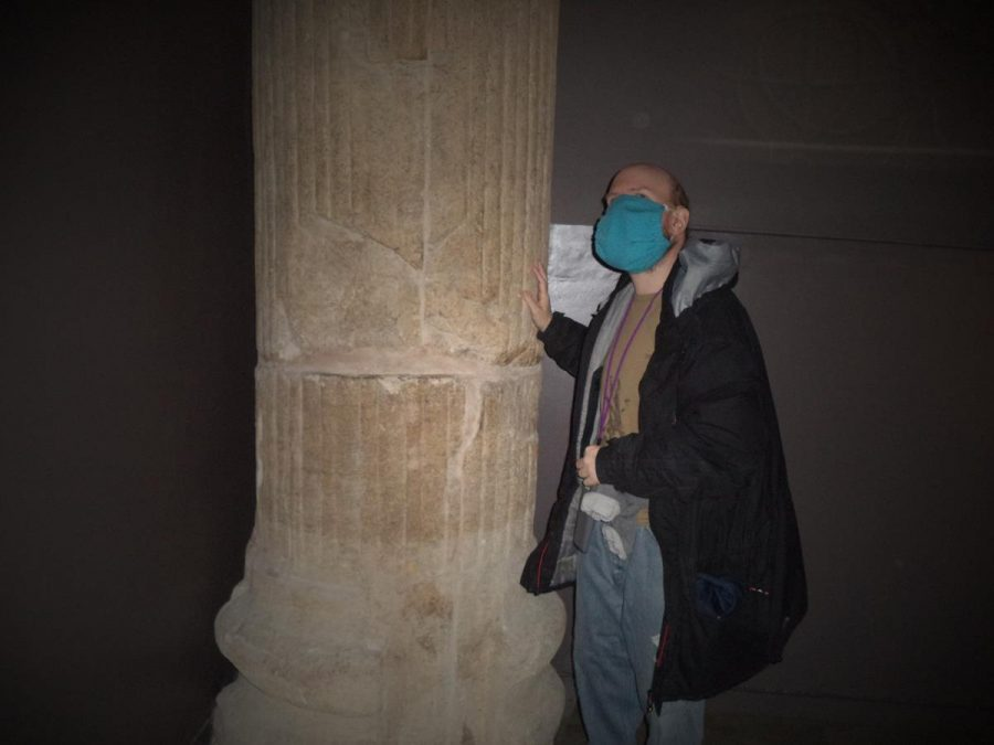 Tony touching the remains of a stone half-column that stands immediately alongside the pediment with the Gorgon's head.