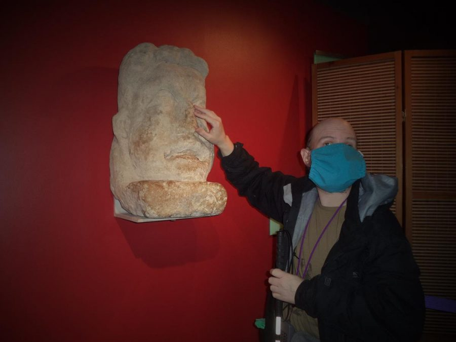 Tony touching a large Roman stone head in the form of a theatrical mask. It is thought to have come from a tomb. The head is male in form and is roughly four times bigger than life size.