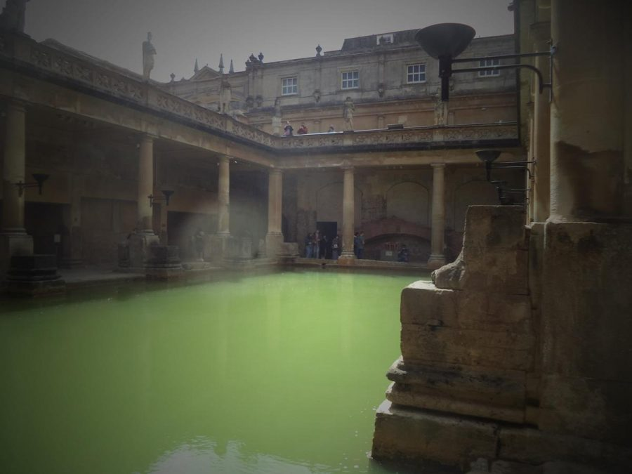 Looking across the pea green water of the Great Bath with the base pedestal of one of the columns in front. People can be seen looking down from a terrace above.