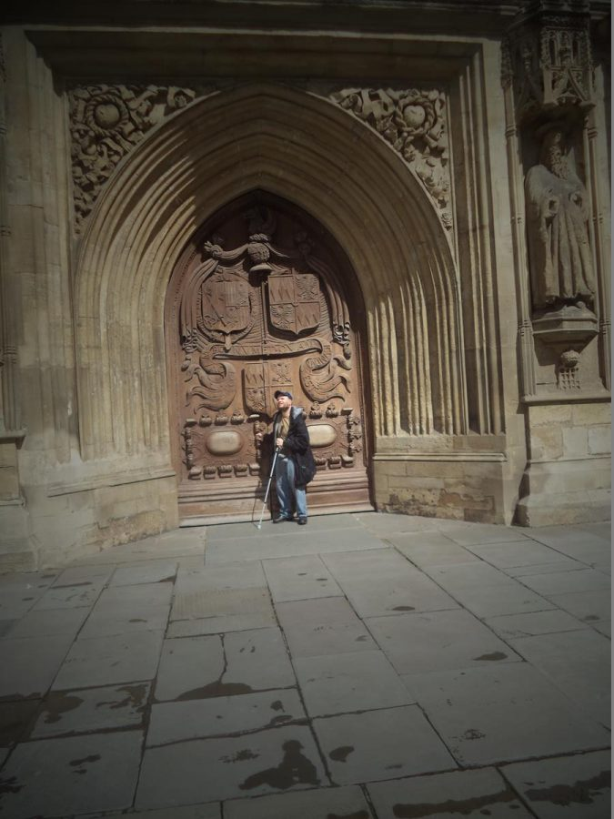 Tony directly in front of the grand West Door of Bath Abbey. These carved wooden double doors bear the coat of arms of the Montague family who donated the doors to the church in 1617. The surrounding stonework includes statues of St Peter and St Paul.