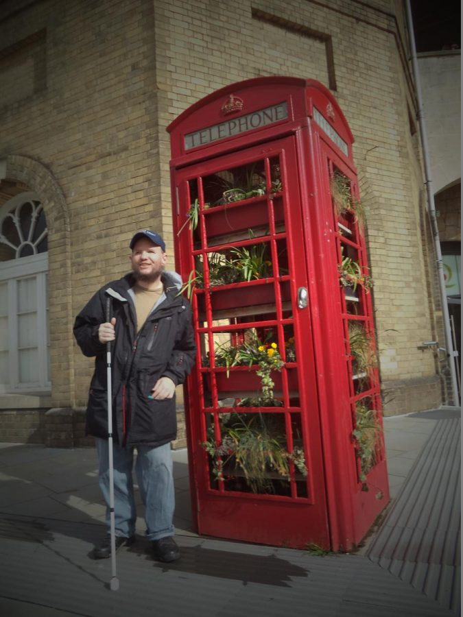 Tony by an old red phone box, which has been filled with colourful flowering plants. Located outside Bath railway station.