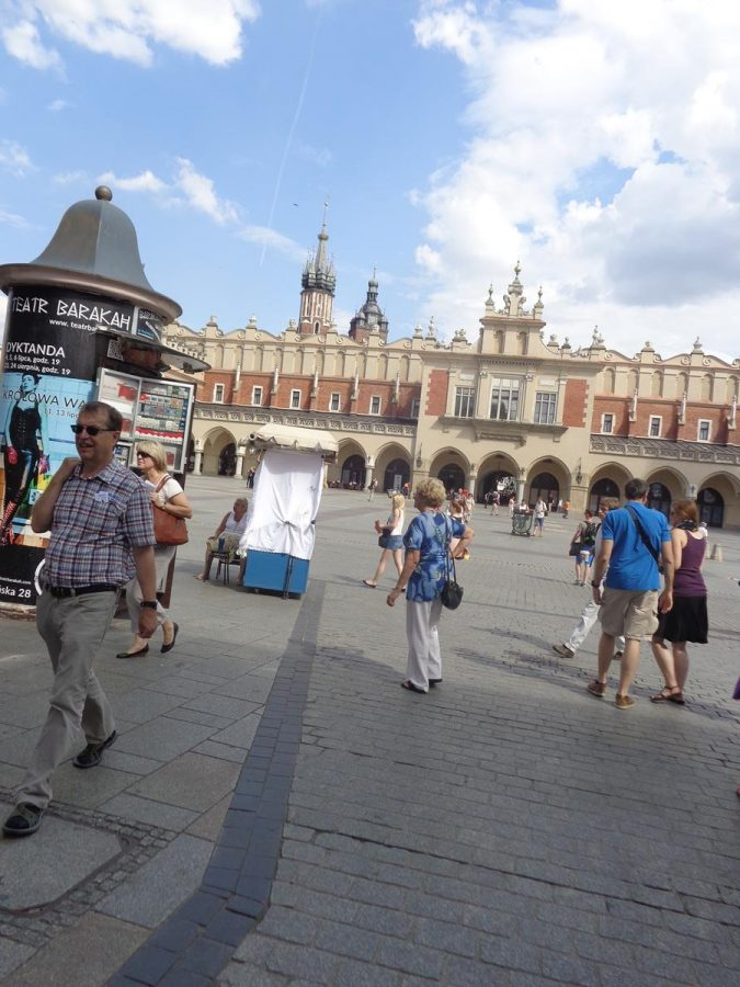 View from the west side of Main Square (Rynek Glówny) towards the Cloth Hall in the middle. Main Square is located in the centre of Kraków's Old Town. It is apparently the largest medieval market square in Europe. The Cloth Hall was originally built in the 14th century as the centre of the cloth trade. It was rebuilt in 1555 in Renaissancestyle. This large and impressive building includes arcades around the outside supported by colonnades and decorative parapets at roof level.