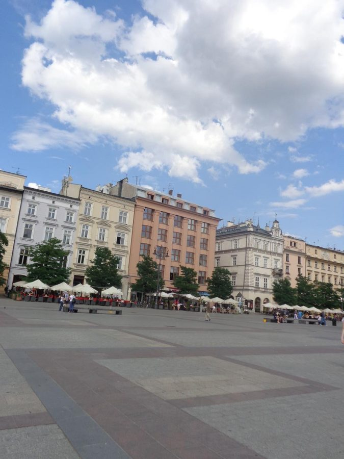 Buildings along the north side of Main Square. These are historic town houses, now mostly neoclassical in style, but often with older structures behind the façades. Many outdoor café and restaurant tables around the edge of the square.