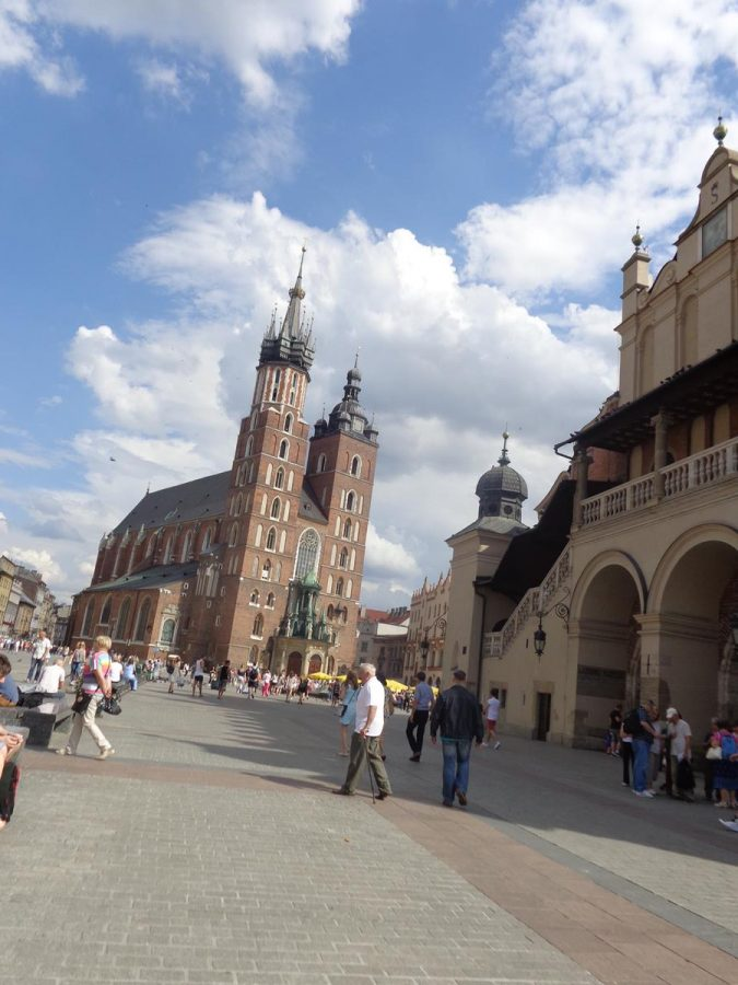 St. Mary's Basilica standing prominently in the north-east corner of Main Square. St. Mary's Basilica (Kosciól Mariacki) is aBrick GothicRoman-Catholic church,which was completed in 1347. Its front façade features a pair of bell towers topped with decorative domes and spires. The north tower (on the left in the photo) is taller than the south tower at 80metres (262feet) in height. The historic centre of Krakow, including this church, has been listed as a UNESCO World Heritage Site since 1978.