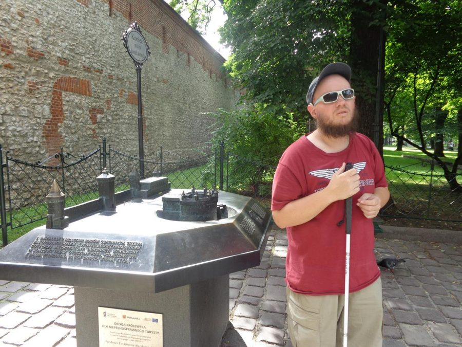 Tony next to a tactile model of both Kraków Barbican and St. Florian's Gate. It shows the Barbican's shape with a roughly semi-circular outer wall topped with seven turrets or watch towers, connected to a smaller rectangular part jutting out towards St. Florian's Gate.