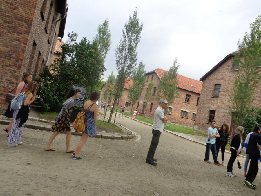 Rows of prison blocks within Auschwitz I camp. These rectangular blocks are two storeys in height and are built of brick with tiled roofs. They are arranged in a grid layout with gravel roads running between.