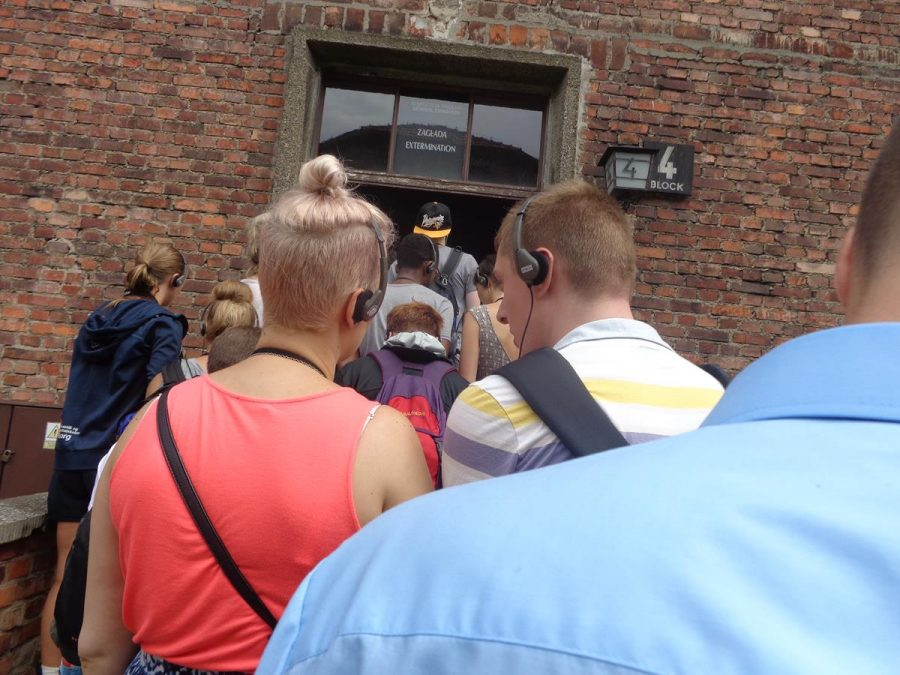 A group of visitors entering through a door into Block 4. This block now contains museum displays documenting the mass extermination of prisoners that was perpetrated at Auschwitz – both Jews and non-Jews. Row upon row of peoples' personal items collected by the Nazis are on display as a stark reminder that it was actual people who were dehumanised and exterminated.