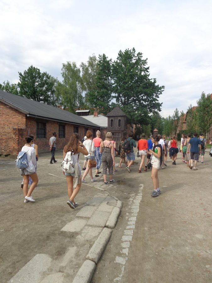 A group of visitors passing by the kitchen building to the left. Beyond, prison blocks partly obscured by trees.