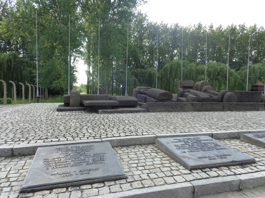 """The International Memorial to the Victims of Auschwitz Camp. This memorial is at the end of the railway line in Auschwitz II-Birkenau concentration camp between the remains of two of the gas chambers and crematoria. In the foreground, a row of stone memorial plaques, all written in different languages but with the same text. The one in view is written in Ukrainian. The English one reads: """"For ever let this place be a cry of despair and a warning to humanity Where the Nazis Murdered about one and a half million men, women and children, mainly Jews from various countries of Europe. Auschwitz-Birkenau 1940-1945"""""""
