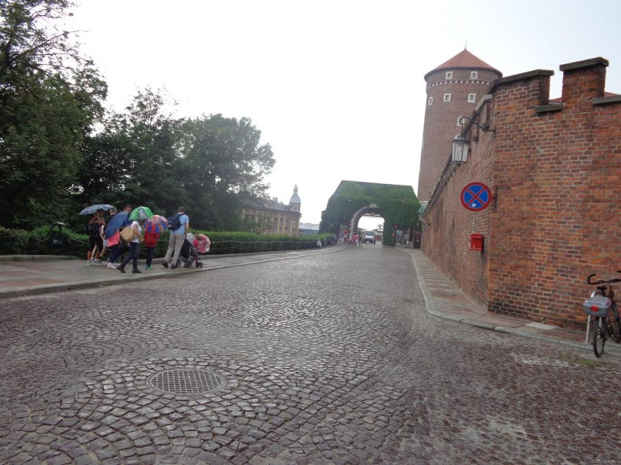A cobbled street leading up to Wawel Hill and Wawel Royal Castle. A crenellated brick outer wall to the right, the historic Bernardynska Gate in front and Sandomierska Tower beyond. Sandomierska Tower is one of the large circular brick artillery towers at Wawel Castle. It dates from the 15th century and was built to defend the castle's southern side.
