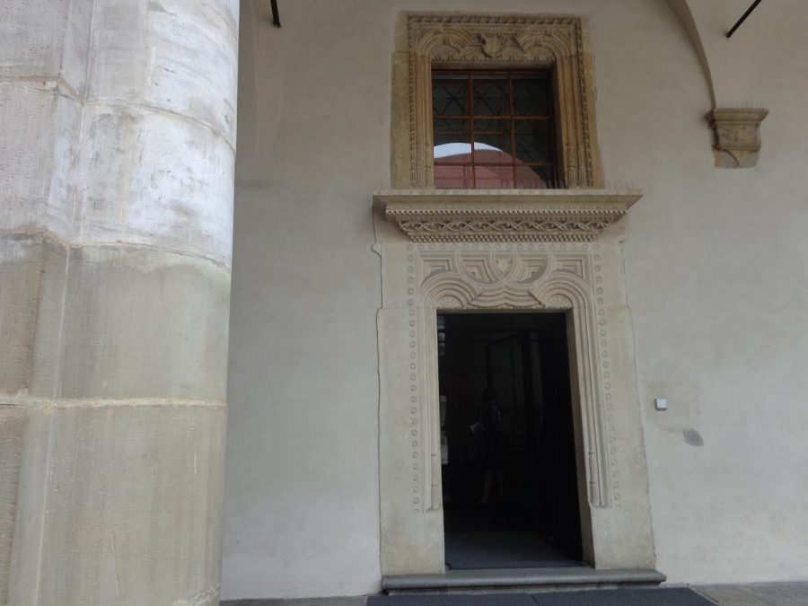 A doorway off the main courtyard with an ornate carved stone surround. The carving is comprised of geometric patterns.