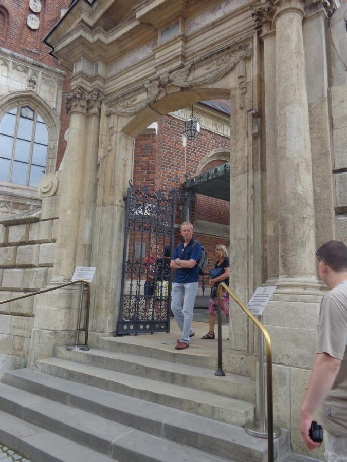A short flight of steps leading up to a gateway with decorative iron gates and a stone surround outside Wawel Cathedral. The gate leads to a small courtyard outside the main entrance.