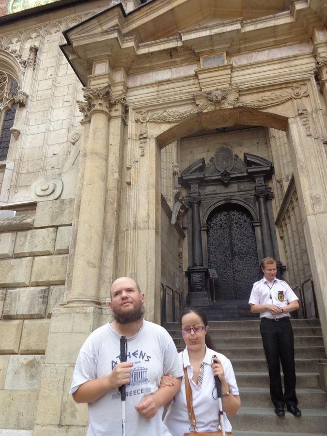 Tony and Tatiana outside the west gate and doorway of Wawel Cathedral. This is a large iron door. Hanging on the left side of the west gate door, suspended from a chain, are large prehistoric animal bones that were found on the site during the excavation process.  It is said that the bones hold magical powers and as long as they are there the cathedral will remain!