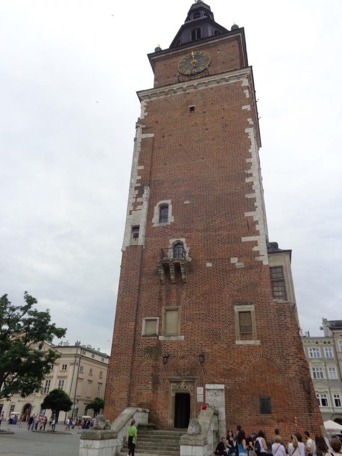 View of the Town Hall Tower. The 70-metre-high tower has a square base with a clock face towards the top of each side. The façade in view has a few irregularly positioned windows with steps leading up to an entrance at the base. It is mostly built of brick with some stone used at the corners and around the windows.