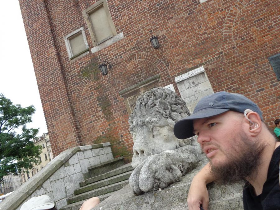 Tony next to a reclining stone lion, one of a pair, which sit on top of retaining walls at either side of steps leading up to the entrance of the Town Hall Tower.