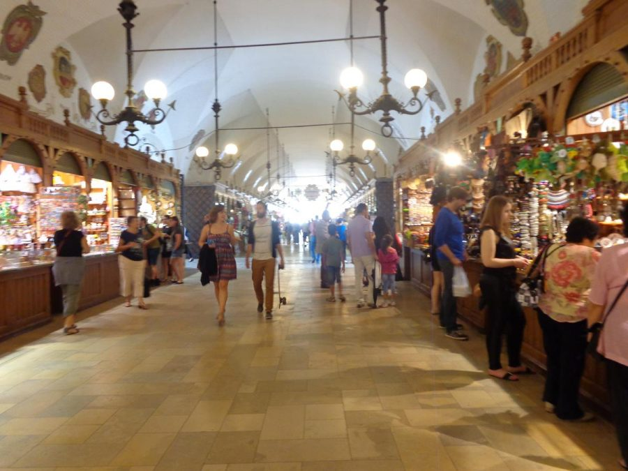 Inside the Cloth Hall looking along a wide passage that runs the whole 110 metre (361 feet) length of the building at ground floor level. The sides are lined with stalls selling a variety of goods: the stalls in view are mostly selling craft items.