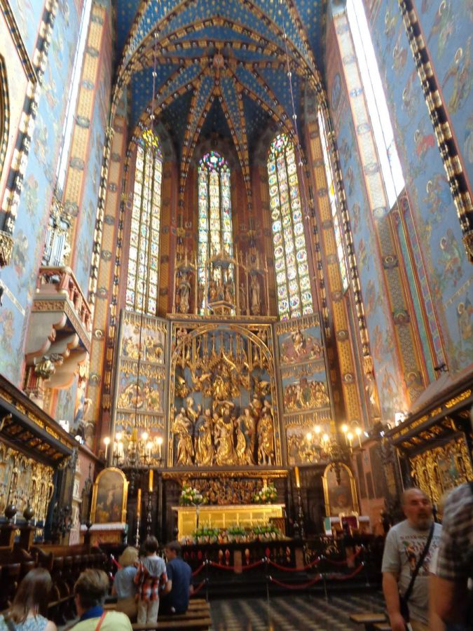 The impressive Gothic main altar inside St. Mary's Basilica. It was carved between 1477 and 1489 by the German-born sculptor Veit Stoss. It is divided into three folding sections that together are 13 metres (42.7 feet) high and 11 metres (36 feet) wide. It depicts several Biblical scenes with the figures and other detail illuminated in gold. Behind are three tall narrow stained-glass windows. The altar was dismantled by the Nazis in 1941 and transported to Germany. It was later recovered in the basement of the heavily bombed Nuremberg Castle and following restoration was put back inside the Basilica.